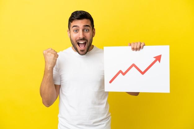 Jovem bonito homem caucasiano isolado em um fundo amarelo segurando uma placa com um símbolo de seta de estatísticas crescentes e comemorando uma vitória