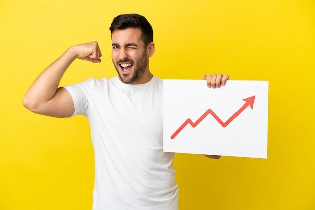 Jovem bonito homem caucasiano isolado em um fundo amarelo segurando uma placa com um símbolo de seta de estatísticas crescentes e fazendo um gesto forte