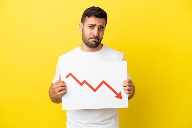 Jovem bonito homem caucasiano isolado em um fundo amarelo segurando uma placa com um símbolo de seta decrescente de estatísticas com uma expressão triste