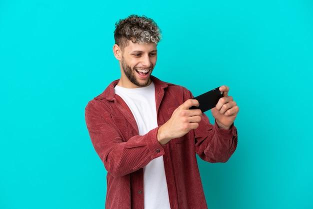 Jovem bonito homem caucasiano isolado em um fundo azul brincando com o celular