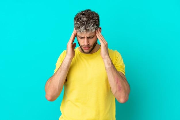Jovem bonito homem caucasiano isolado em um fundo azul com dor de cabeça
