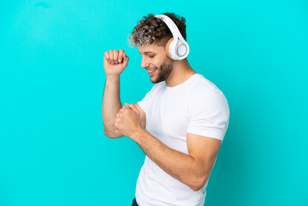 Jovem bonito homem caucasiano isolado em um fundo azul ouvindo música e dançando