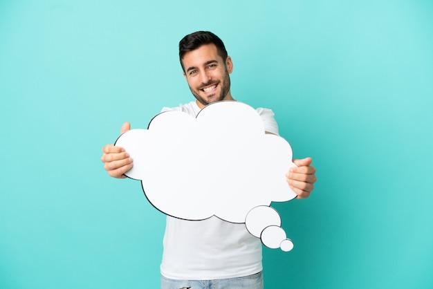 Jovem bonito homem caucasiano isolado em um fundo azul segurando um balão de pensamento