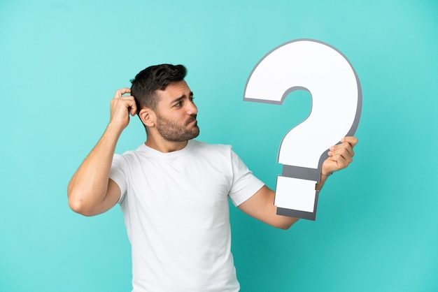 Jovem bonito homem caucasiano isolado em um fundo azul segurando um ícone de ponto de interrogação e tendo dúvidas