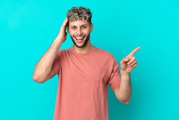 Jovem bonito homem caucasiano isolado em um fundo azul surpreso e apontando o dedo para o lado