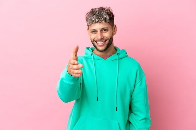 Jovem bonito homem caucasiano isolado em um fundo rosa apertando as mãos para fechar um bom negócio