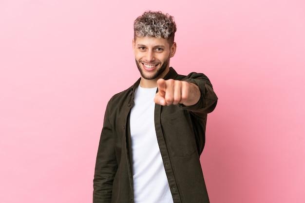Jovem bonito homem caucasiano isolado em um fundo rosa apontando para a frente com uma expressão feliz