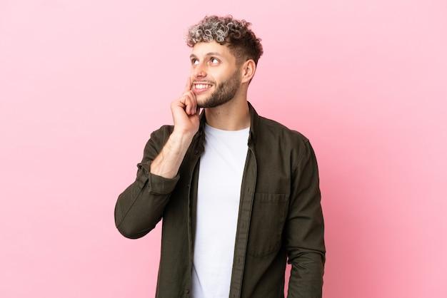 Jovem bonito homem caucasiano isolado em um fundo rosa pensando em uma ideia enquanto olha para cima