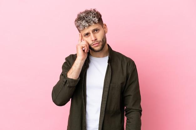 Jovem bonito homem caucasiano isolado em um fundo rosa pensando em uma ideia.