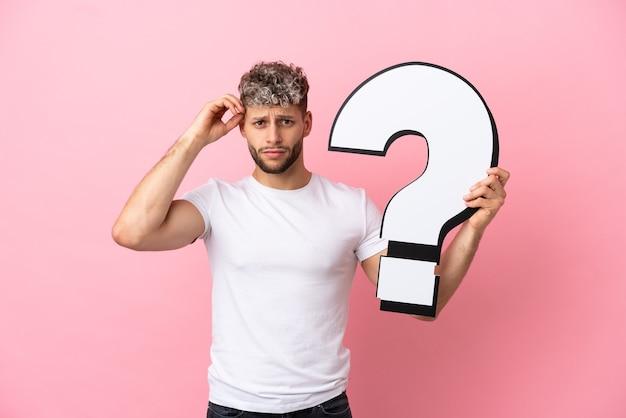 Jovem bonito homem caucasiano isolado em um fundo rosa segurando um ícone de ponto de interrogação e tendo dúvidas