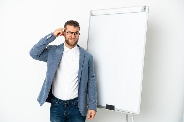 Jovem bonito homem caucasiano isolado no fundo branco fazendo uma apresentação no quadro branco e tendo dúvidas com a expressão facial confusa