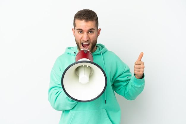 Jovem bonito homem caucasiano isolado no fundo branco gritando através de um megafone para anunciar algo e com o polegar para cima