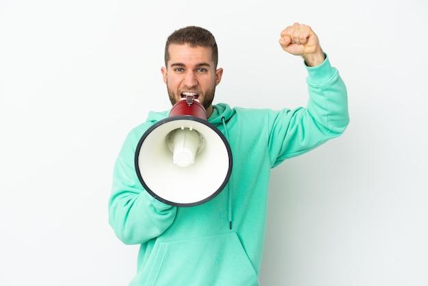 Jovem bonito homem caucasiano isolado no fundo branco gritando em um megafone para anunciar algo