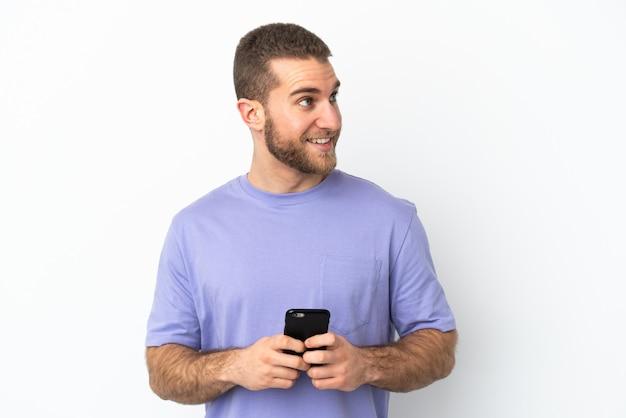 Jovem bonito homem caucasiano isolado no fundo branco usando telefone celular e olhando para cima