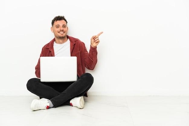Jovem bonito homem caucasiano sentado no chão com laptop apontando o dedo para o lado