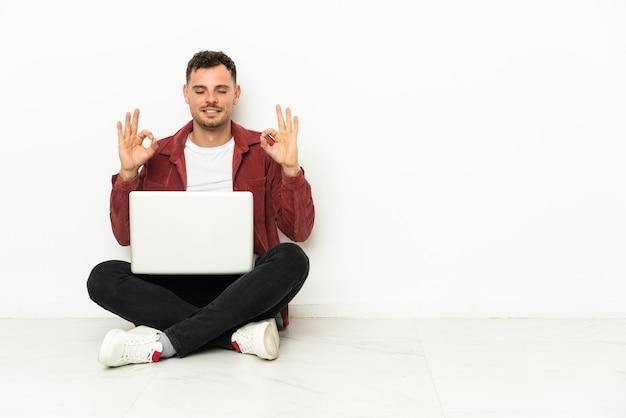 Jovem bonito homem caucasiano sentado no chão com o laptop em pose zen