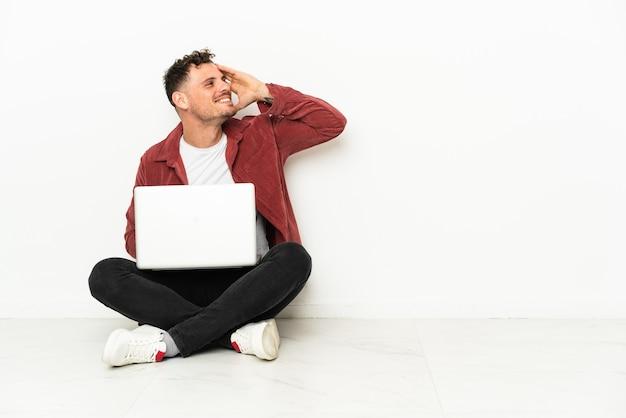 Jovem bonito homem caucasiano sentado no chão com um laptop percebeu algo e pretendendo a solução