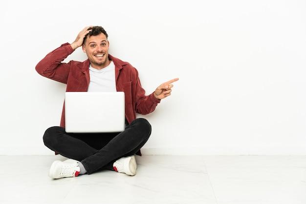 Jovem bonito homem caucasiano sentado no chão com um laptop surpreso e apontando o dedo para o lado