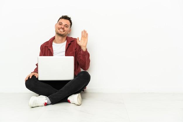 Jovem bonito homem caucasiano sentado no chão com um laptop