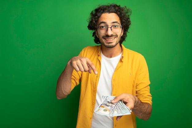 Jovem bonito homem caucasiano sorridente usando óculos, segurando e apontando para o dinheiro isolado na parede verde com espaço de cópia