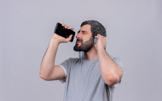 Jovem bonito homem caucasiano usando fones de ouvido finge cantar e usando seu telefone celular como microfone com os olhos fechados e a mão no fone de ouvido isolado no fundo branco com espaço de cópia