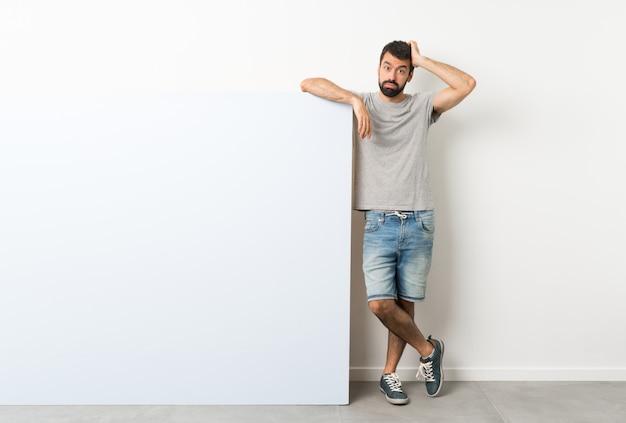 Jovem bonito homem com barba, segurando um grande cartaz vazio azul com uma expressão de frustração e não compreensão