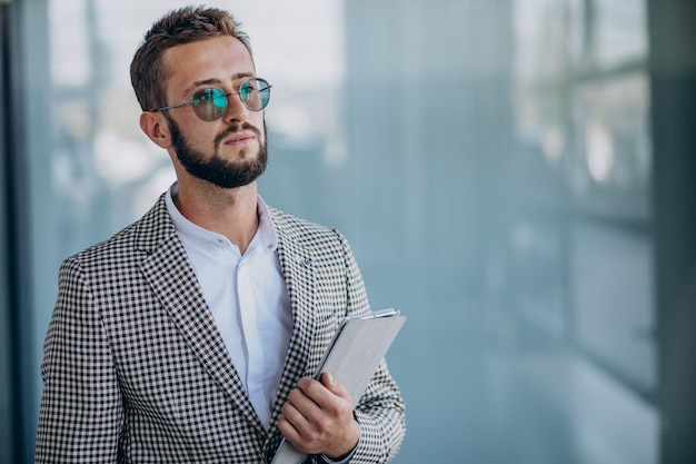 Jovem bonito homem de negócios no escritório segurando um tablet