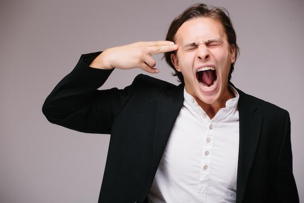 Jovem bonito homem de negócios usando terno e gravata sobre uma parede isolada, atirando e se matando apontando a mão e os dedos para a cabeça como uma arma