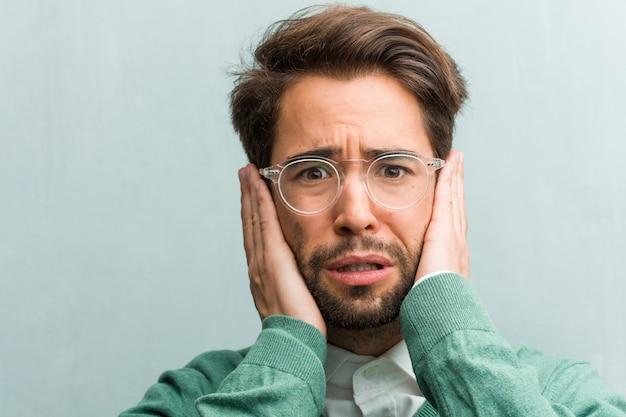 Jovem, bonito, homem empreendedor, rosto, closeup, cobertura, orelhas, com, mãos