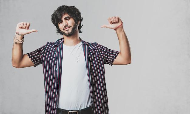 Jovem bonito homem orgulhoso e confiante, apontando os dedos, exemplo a seguir, o conceito de sa
