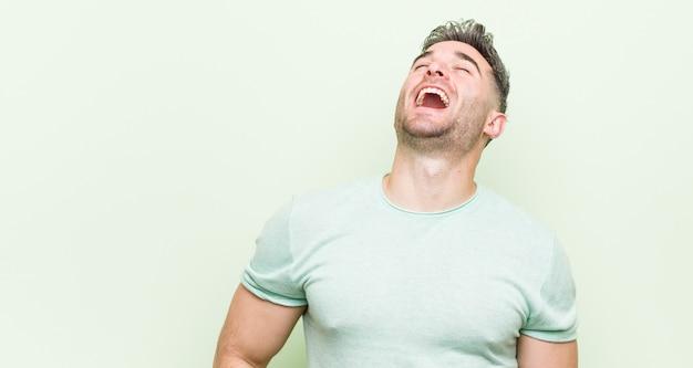 Jovem bonito homem relaxado e feliz rindo, pescoço esticada, mostrando os dentes.