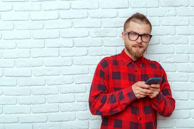 Jovem, bonito, homem, usando, telefone móvel, enquanto, inclinar-se, parede tijolo