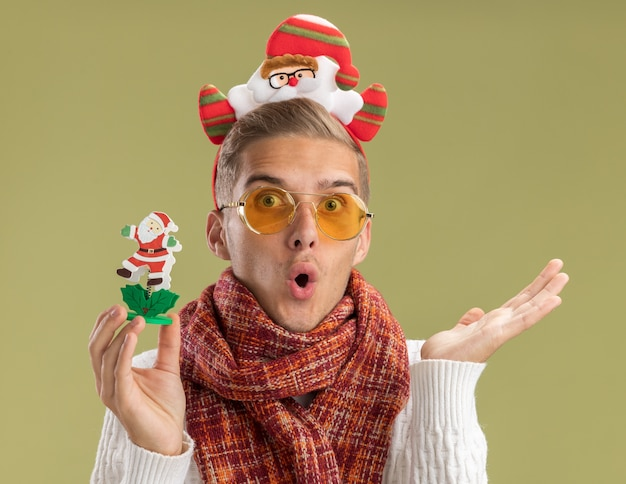 Jovem bonito impressionado com bandana de papai noel e cachecol, olhando para a câmera segurando um brinquedo de papai noel, mostrando a mão vazia isolada em fundo verde oliva