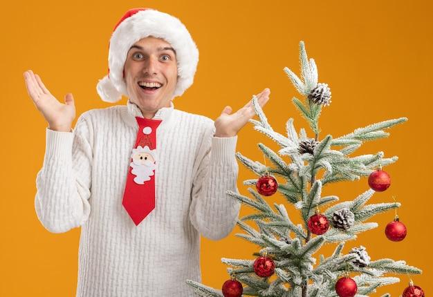 Jovem bonito impressionado com chapéu de natal e gravata de papai noel em pé perto da árvore de natal decorada, mostrando as mãos vazias isoladas na parede laranja