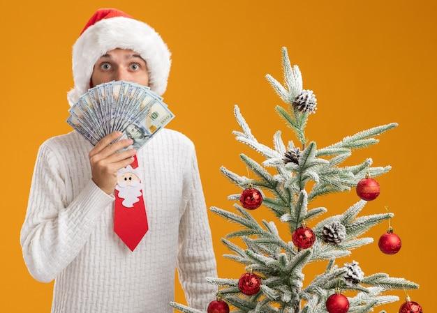 Jovem bonito impressionado com chapéu de natal e gravata de papai noel em pé perto de uma árvore de natal decorada segurando dinheiro por trás dele, isolado em uma parede laranja