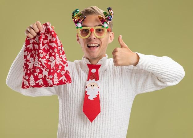 Jovem bonito impressionado com óculos de natal e gravata de papai noel, segurando um saco de natal, olhando para a câmera aparecendo o polegar isolado no fundo verde oliva