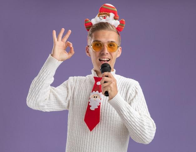 Jovem bonito impressionado usando bandana de papai noel e gravata com óculos segurando o microfone perto da boca, olhando para a câmera, fazendo sinal de ok isolado no fundo roxo
