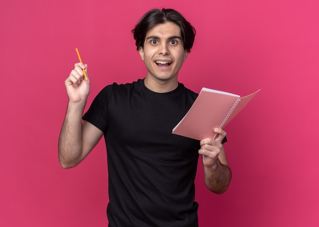 Jovem bonito impressionado, vestindo uma camiseta preta, segurando um caderno com lápis - isolado na parede rosa