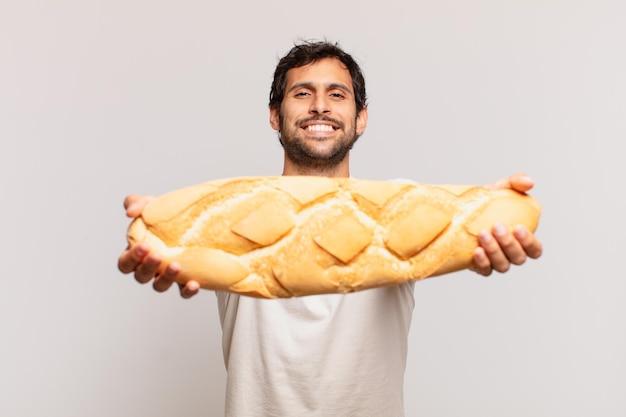 Jovem bonito indiano com expressão feliz e segurando um pão