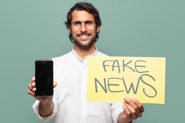 Jovem bonito indiano mostrando a tela do celular. conceito de notícias falsas
