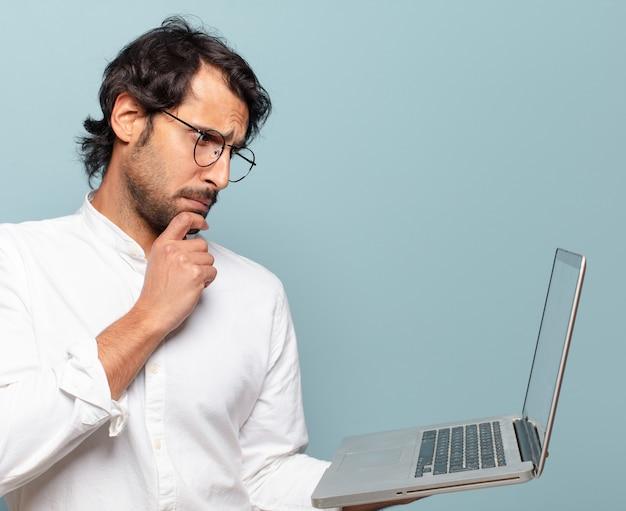 Jovem bonito indiano segurando um laptop. conceito de negócios ou mídia social