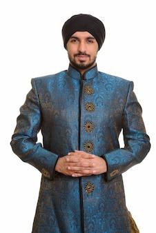 Jovem bonito indiano sikh entrelaçando os dedos vestindo