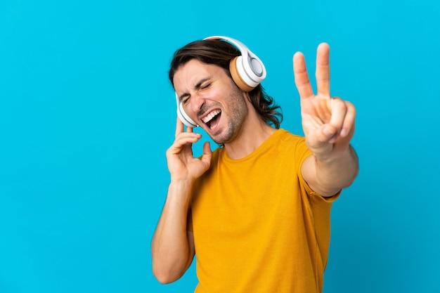 Jovem bonito isolado em um fundo azul ouvindo música e cantando