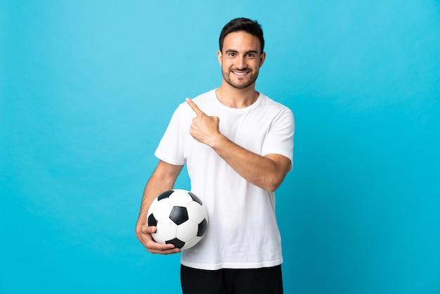 Jovem bonito isolado em uma parede azul com uma bola de futebol apontando para a lateral