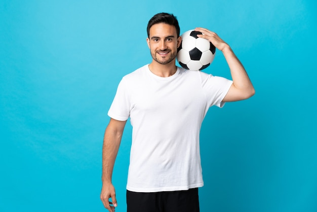 Jovem bonito isolado na parede azul com uma bola de futebol