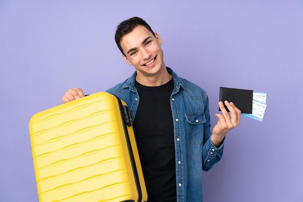 Jovem bonito isolado na parede roxa em férias com mala e passaporte