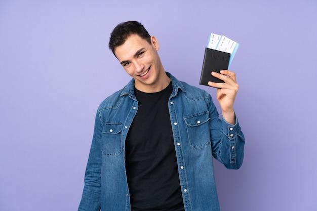 Jovem bonito isolado na parede roxa feliz em férias com bilhetes de avião e passaporte