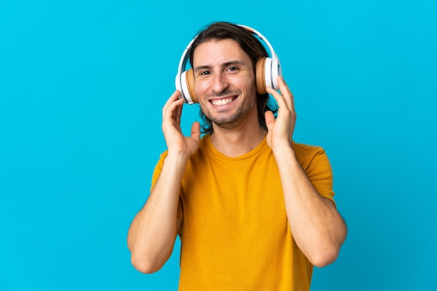 Jovem bonito isolado ouvindo música azul