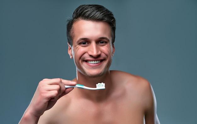 Jovem bonito isolado. retrato de homem musculoso sem camisa está de pé sobre um fundo cinza com escova e pasta de dentes na mão e sorrindo. conceito de cuidados de homens.