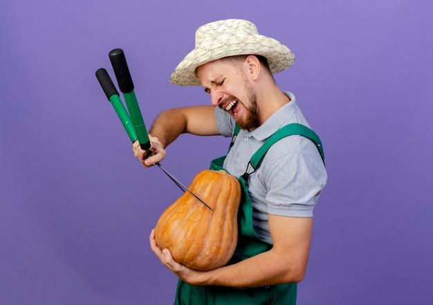 Jovem bonito jardineiro eslavo de uniforme e chapéu em pé na vista de perfil segurando abóbora e podadores cortando abóbora isolada